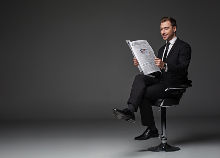 Full length portrait of outgoing bearded worker looking trough article while locating on seat. Relax concept. Copy space