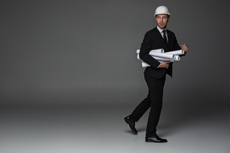 Full length portrait of troublous bearded builder holding rolls of paper while in hurry to work. Profession concept. Copy space