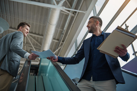 Low angle of two young cheerful guys are moving on escalators and transferring document to each other with smile. They are holding paper together Stock Photo