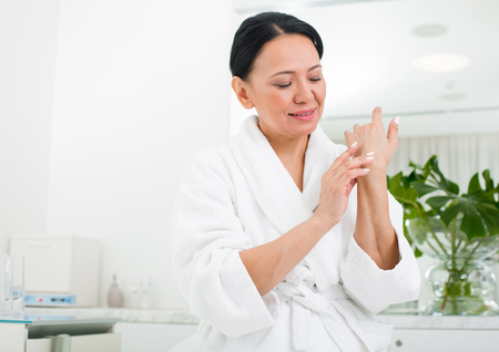 Waist up portrait of tranquil senior lady putting cream on hand with her finger. She is looking at her arms and sitting at spa
