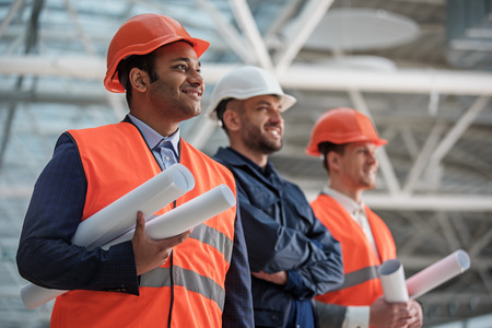 Cheerful young builders are working on building of construction. Men in helmets are standing and holding blueprints. They are looking aside with inspiration and smile. Selective focus Reklamní fotografie