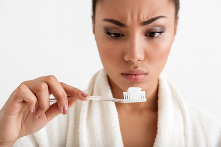 Close up of woman face looking at toothpaste with puzzlement. Focus on hand holding toothbrush. Isolated on background
