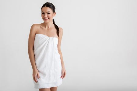 Portrait of fit woman standing in the towel. She is looking at camera with smile. Copy space in right side. Isolated on background