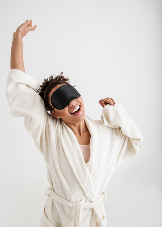 Waist up portrait of fresh woman with blindfold waking up. She is stretching herself with joy and yawning. Isolated on background Stock Photo