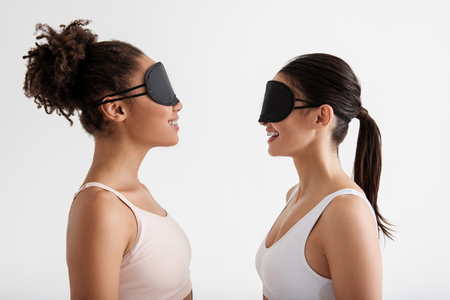 Side view profile of laughing girls wearing blindfolds while standing opposite. Isolated on background