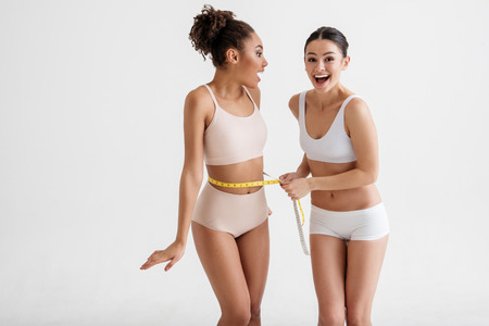 Glad slim girls standing in underwear and taking measurements of each other. Their faces expressing joy. Copy space in left side. Isolated on background Imagens - 94345122