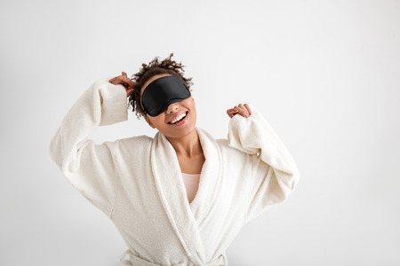 Waist up portrait of happy woman stretching up after dream. She is wearing sleeping mask. Isolated on background