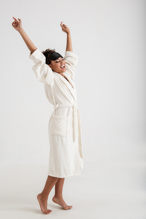 Pleased girl with slim body standing in bathrobe. She is holding her hands up and gaping