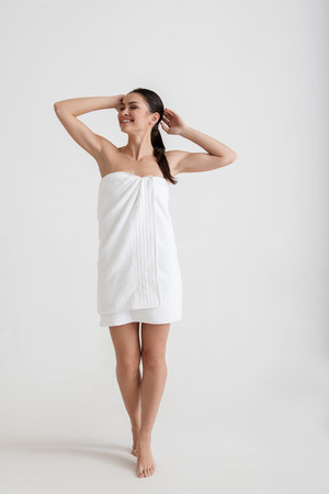 Cleanliness concept. Full length portrait of happy woman posturing in the towel wrapped around her slim figure. Isolated on background