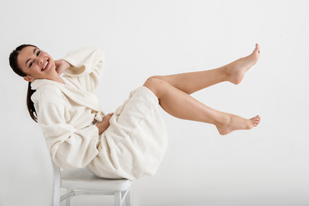 Satisfied girl in bathrobe sitting on chair and showing her fit legs. Isolated on background
