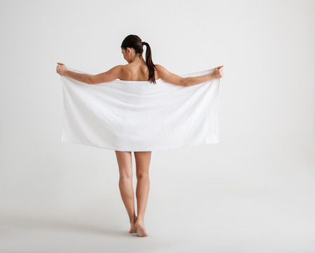 Undressed calm girl standing with her back. She is hiding her graceful body behind a towel. Isolated on background