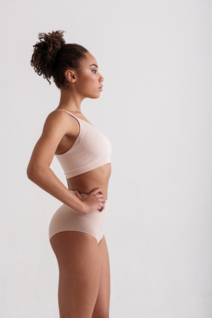 Side view profile of tranquil slim girl watching her weight. She is demonstrating her slender figure. Copy space in right side. Isolated on background Stock Photo