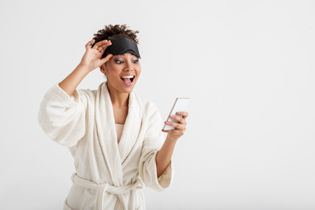 Waist up portrait of african woman wearing terry robe and blindfold on forehead. She is using cellphone with joy. Copy space in right side. Isolated on background