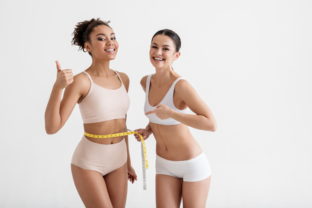 Portrait of skinny young women standing in lingerie and smiling. They are showing the result of measurement. Isolated on background