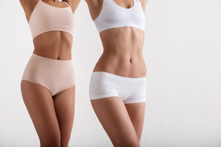 Slender young girls showing their slim forms after a longtime healthy diet. Isolated on background Stock Photo