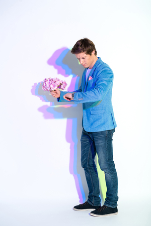 Full length portrait of concentrated male looking at watch. He carrying beautiful nosegay in arm. Date concept Stock Photo