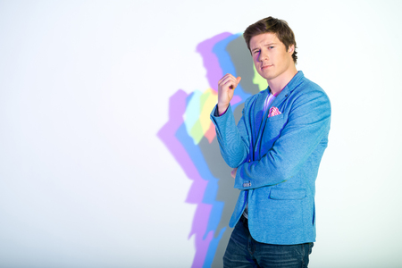 Portrait of smiling man standing with multicolored shadow looking at camera. Copy space. Happiness concept