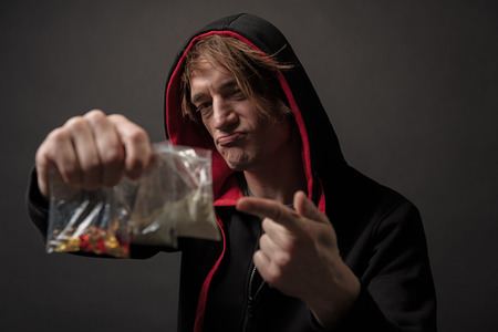 Portrait of untidy serious male showing drugs in plastic containers, he is pointing at them with his finger. Focus on man. Isolated on background