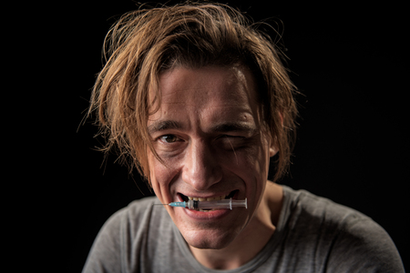 Portrait of happy junked up man with empty squirt in mouth looking at camera. Isolated on background