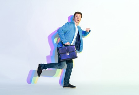 Full length portrait of amazed male hurrying to job. He holding suitcase. Late for labor concept Reklamní fotografie