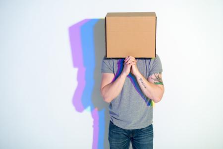 Mens met karton op hoofd die terwijl het bekijken camera smeekt. Veelkleurige schaduw lokaliseren op muur. Entreaty concept. Kopieer ruimte Stockfoto