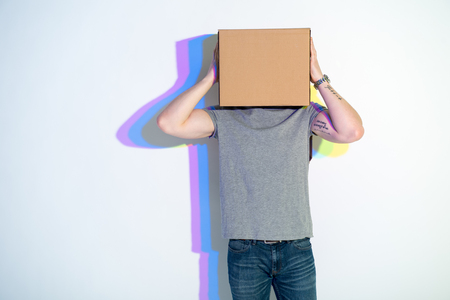 Man with carton on head holding it by arm. Multicolored shadow locating on wall. Creativity concept
