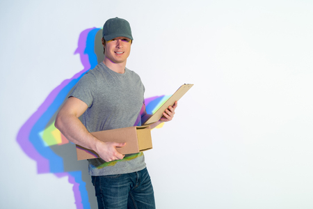 Portrait of cheerful postman holding package while looking in camera. Multicolored shadow locating on wall. Conveyance concept. Copy space Stock Photo
