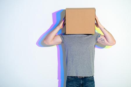 Man putting carton box on head. Multicolored shadow locating on wall. Creativity concept Standard-Bild
