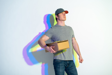 Side view confident male with multicolored shadow holding parcel in hands. Delivery concept