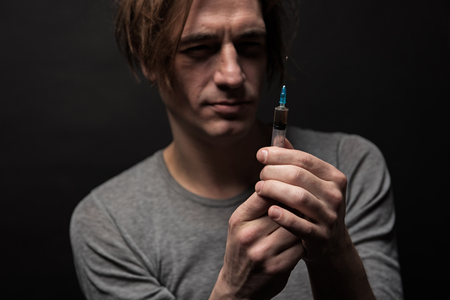 Portrait of serious male filling hype with narcotic substance with concentrated face. Focus on syringe. Isolated on background Stock Photo