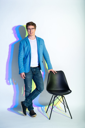 Full length portrait of happy male with multicolored shadow situating near seat. Cheerfulness concept
