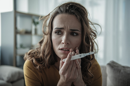 Frightened girl is shocked about her pregnant state. Focus on pregnancy test stick with two strips on it. Portrait Stock Photo