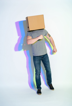 Full length man with carton on head flourishing arms. Multicolored shadow locating on wall. Creativity concept