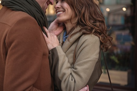 Close up of affectionate man touching female face with gentleness. Woman is looking at into his eyes and smiling. Lovers are standing and hugging on street Stock Photo
