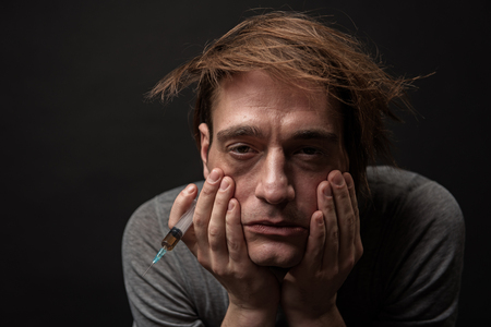Portrait of depressed habit man with bushy hair holding syringe in his hand. Isolated on background Stock Photo