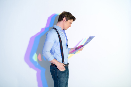 Side view of undistracted man looking through newspaper. Painted reflection reflecting on wall. Publication concept
