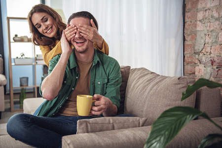Guess who it is. Joyful young woman is closing male eyes secretly. Intrigued man is smiling while sitting on sofa and holding cup Foto de archivo