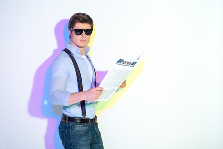 Portrait of determined young male holding article in hands. He looking at camera. Multicolored shadow. Press concept