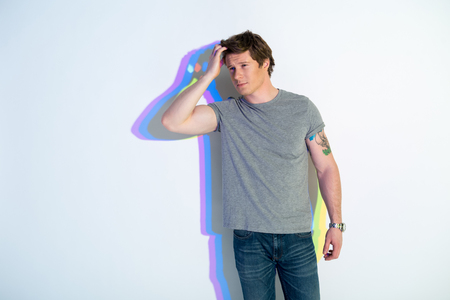 Portrait of pensive man touching hair. Multicolored shadow reflecting on wall. Dreaminess concept. Copy space Stock Photo