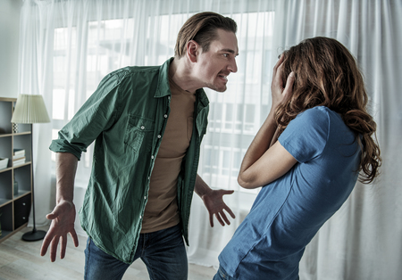 Irritated husband is shouting at his wife with violence. Woman is covering her face with fear Stock Photo