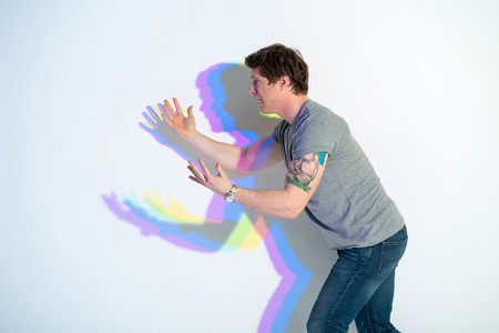 Oh no. Side view depressed man with multicolored shadow flourishing arms