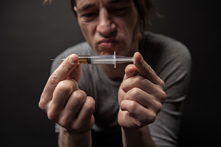 Stressed addict holding syringe with drugs inside, he is looking at it with doubt. Focus on hands with instrument. Isolated on background