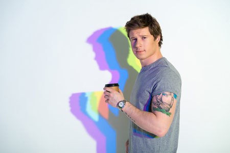 Portrait of smiling man with multicolored shadow drinking cup of delicious beverage. Rest concept. Copy space