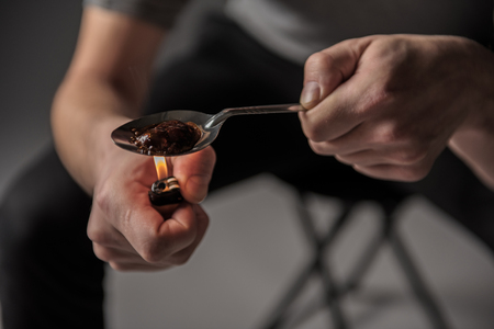 Abuse concept. Close up of male hands holding and heating teaspoon with junk on fire Stock Photo