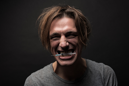 Portrait of grubby cheerful guy clutching syringe between teeth with happy grin. Isolated on background