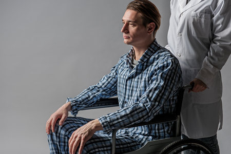Depressed disabled taking seat in armchair. He is nursed by invalid tender. Isolated on background Stock Photo