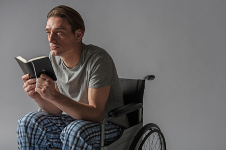 Thoughtful unhealthy man sitting in wheelchair with holy book in hands. Copy space in right side. Isolated on background Stock Photo
