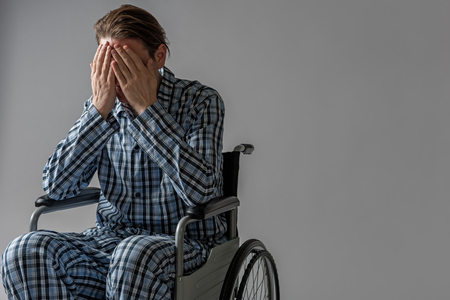 Decadent male person sitting in wheelchair and covering his face with hands. He is crying. Copy space in right side. Isolated on background Stock Photo