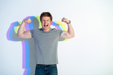 Portrait of cheerful man putting out tongue while demonstrating biceps. Sport concept. Copy space