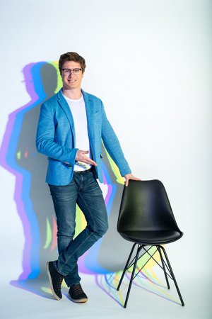Full length portrait of cheerful man demonstrating modern chair while standing near it. Modern furniture concept